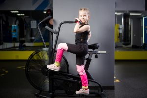 Small attractive caucasian child using exercise bike in the gym. Fitness. A little athlete using an air bike for a cardio workout at the crossfit gym. Sport girl sitting on bicycle machine